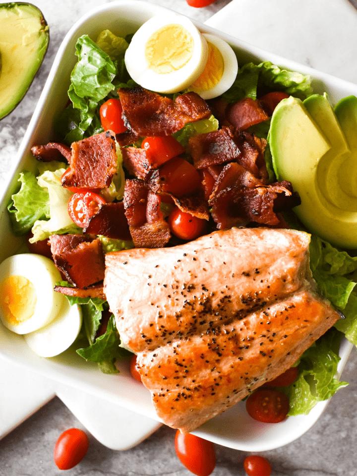 Large salad with bacon, tomato, egg, avocado and honey mustard