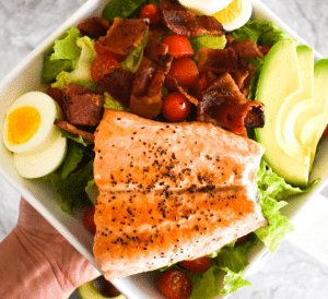 Large salad with bacon, egg, avocado, tomato and honey mustard