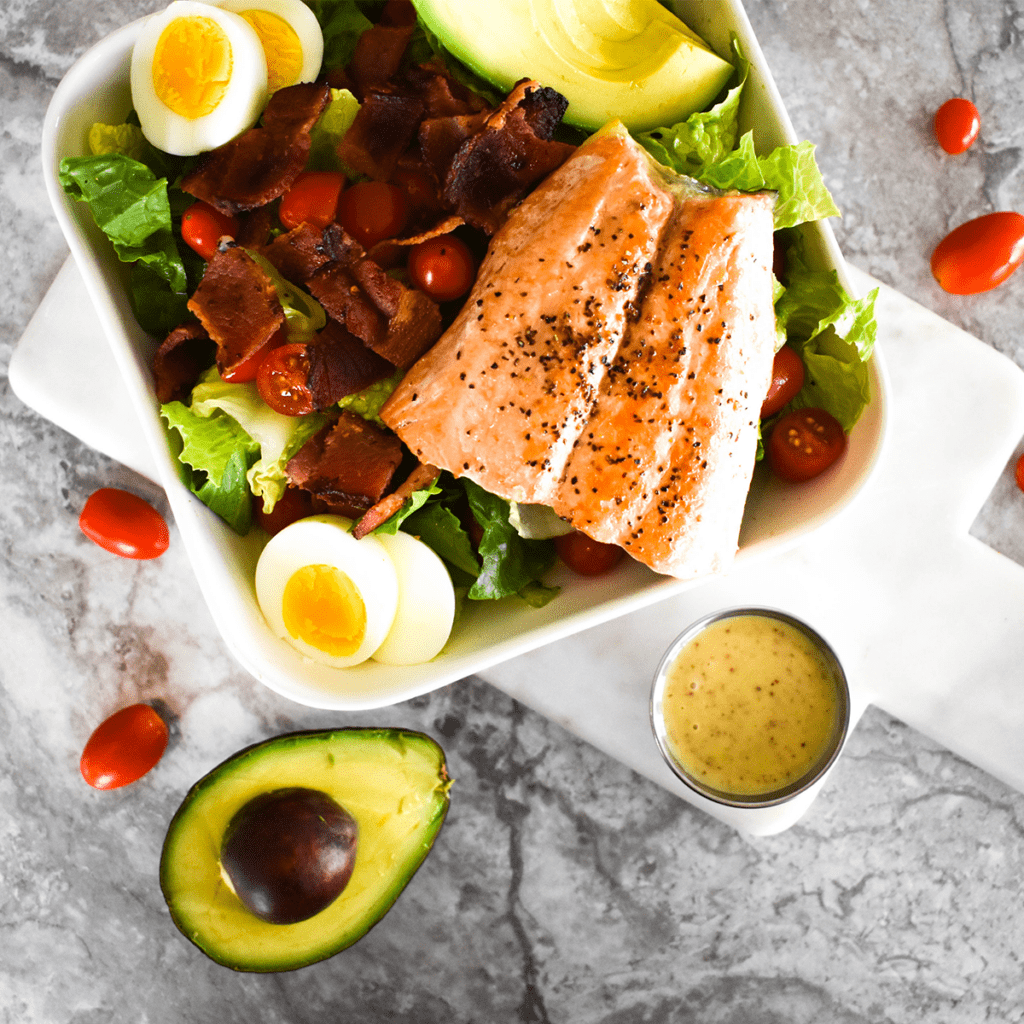 Large salad with bacon, tomato,egg, avocado and honey mustard