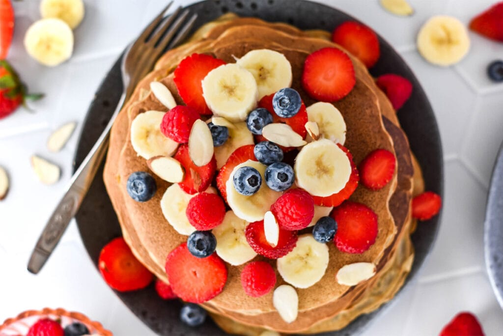 Stack of paleo banana flour pancakes topped with lots of banana, blueberries, strawberries and raspberries.