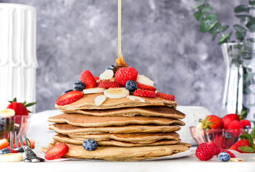 Stack of paleo pancakes topped with lots of banana, blueberries, strawberries and raspberries.
