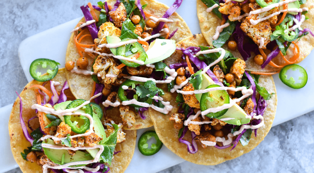 Close up of tacos with avocado, kale, cabbage, chickpeas and cauliflower