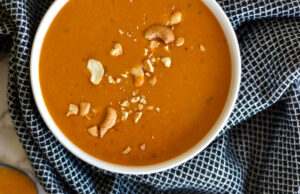 Top down view of paleo curry butternut squash soup in white bowl.