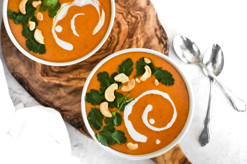 Two bowls of bright orange paleo curry butternut squash soup with cilantro, coconut cream and cashews on top.