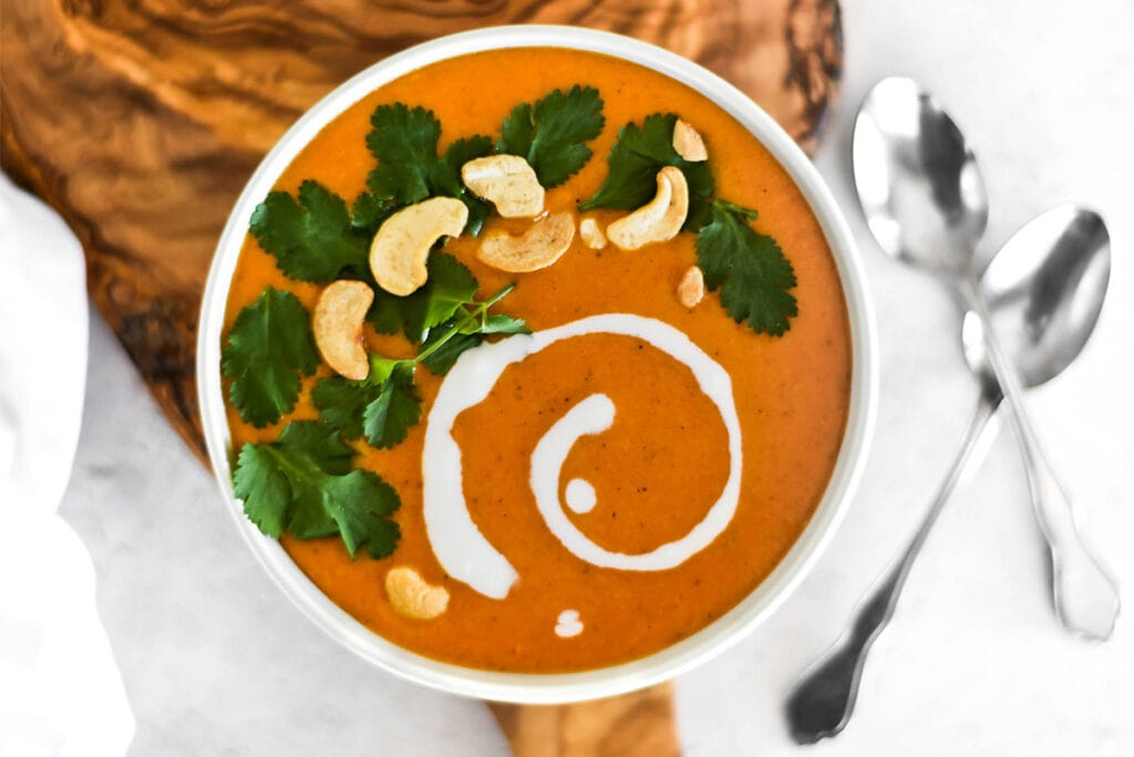 Bowl of bright orange curry butternut squash soup with cilantro, coconut cream and cashews on top.