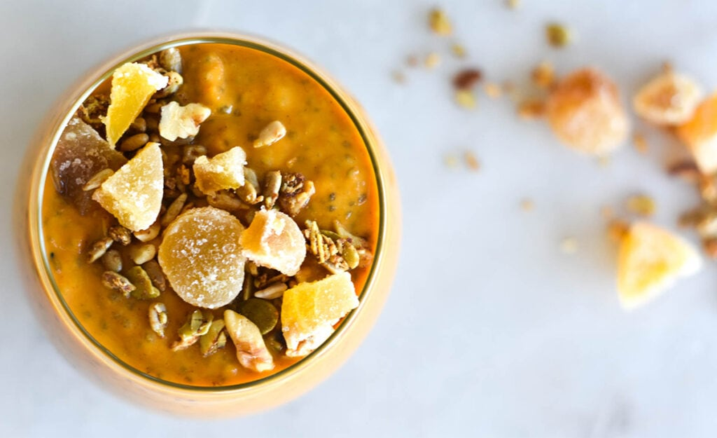 Top down view of bright orange pumpkin chia pudding on cutting board next to spice and nuts.