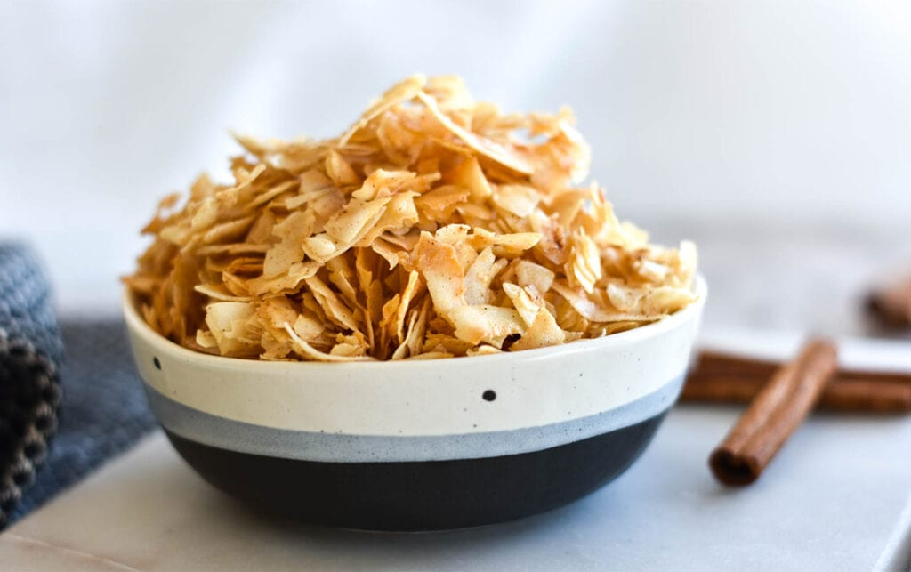Bowl of coconut chips next to cinnamon sticks