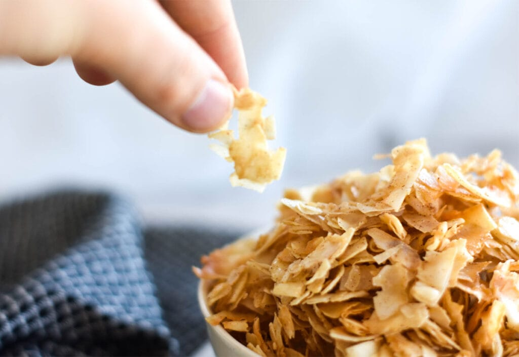 hand grabing coconut chips from bowl