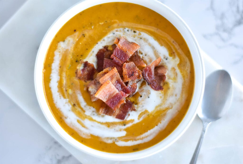 Thick bowl of orange soup topped with chunks of bacon and coconut cream.