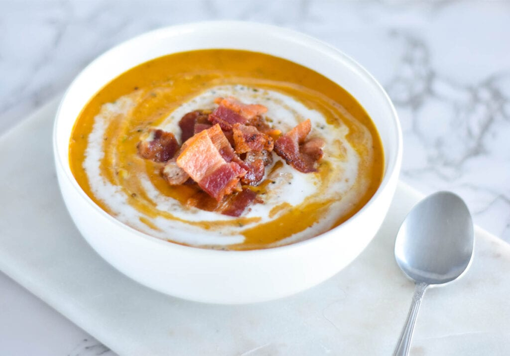 White bowl of orange sweet potato soup topped with a pile of bacon and coconut cream.