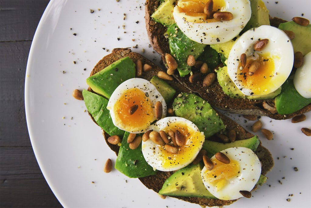 Toast with avocado, soft boiled eggs and pine nuts.