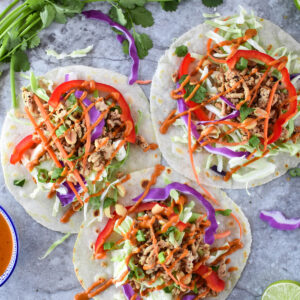Colorful Thai Tacos with purple cabbage, ground chciken, red bell peppers and cilantro.