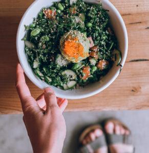 Girl holding bowl of vegetables