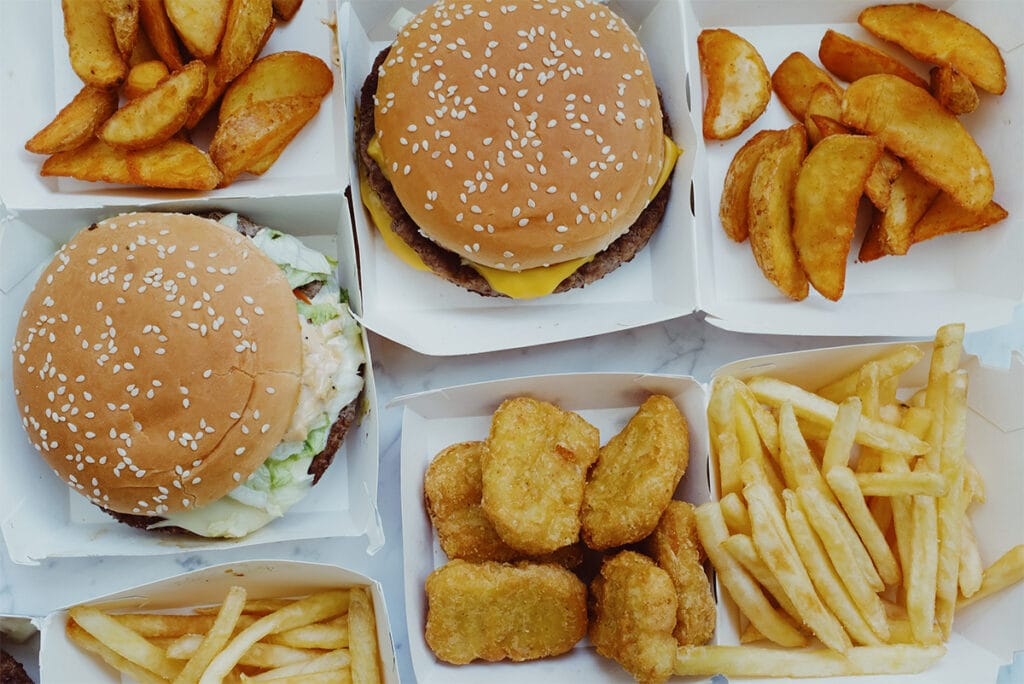 Fast food spread with chicken nuggets, burgers and fries.