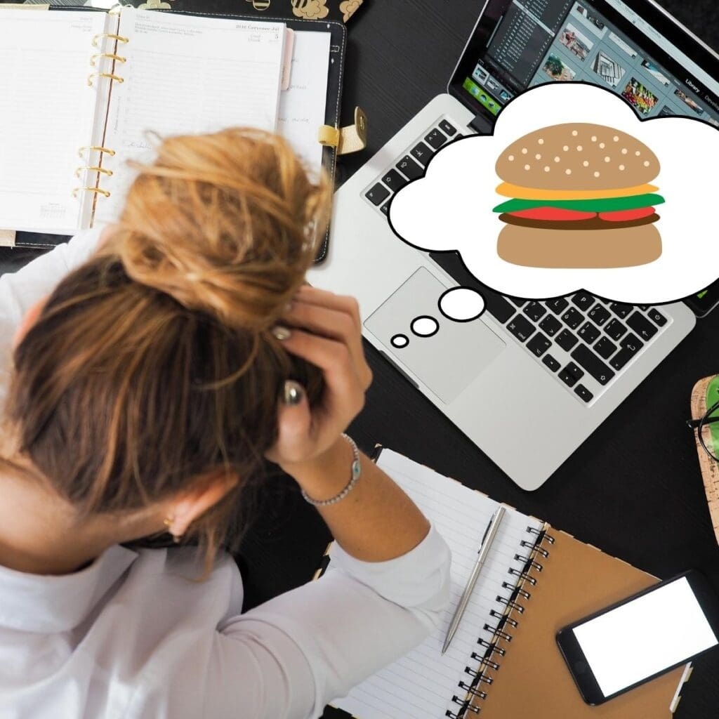 Girl looking stressed out over her computer. She has a thought bubble with a cheeseburger in it.