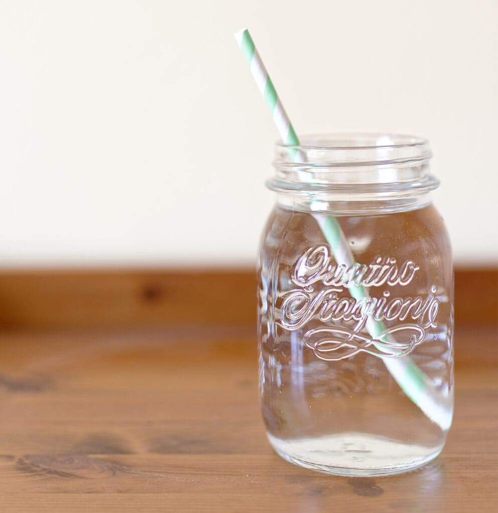 mason jar filled with water and straw