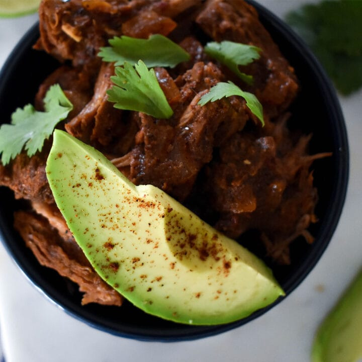 Top down view of barbacoa in bowl with avocado and cilantro.