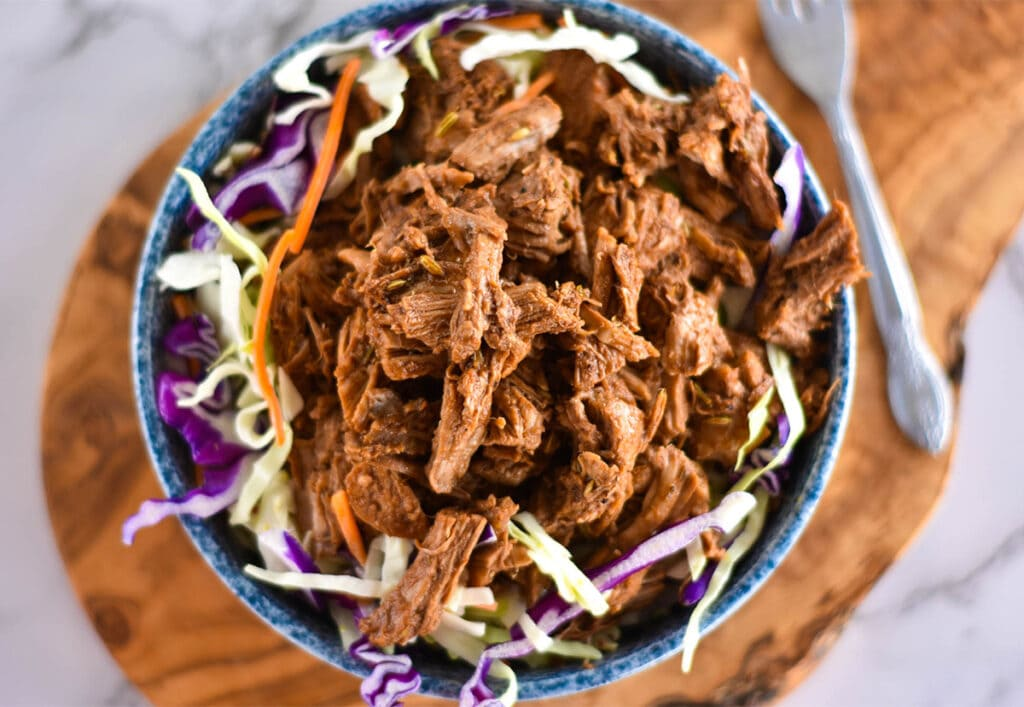 Top down view of blue bowl on a wooden cutting board, filled with coleslaw and pulled pork.