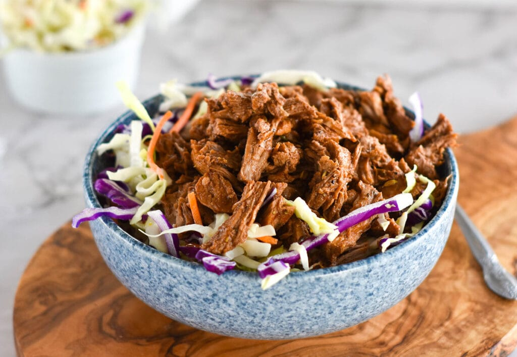 Blue bowl of pulled pork with coleslaw on a wooden serving board.