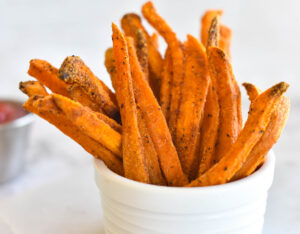 White bowl filled with sweet potato fries.