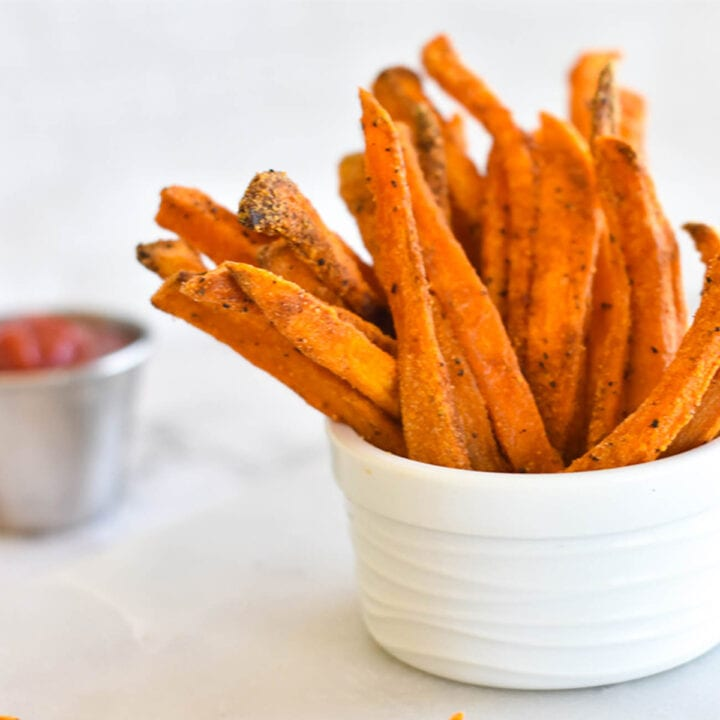 Crispy Paleo Baked Sweet Potato Fries in a bowl next to ketchup.