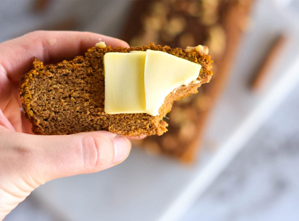 hand holding a piece of keto pumpkin bread with bite out of it