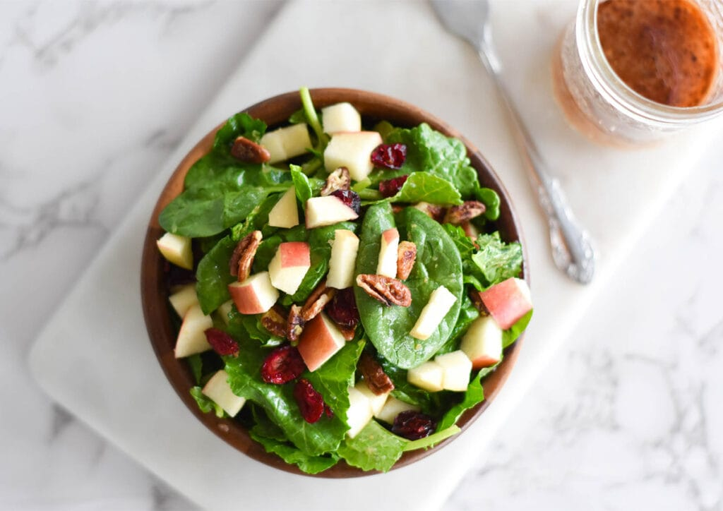 Wooden bowl full of spinach and kale with apples, pecans and cranberries next to a jar of dressing.