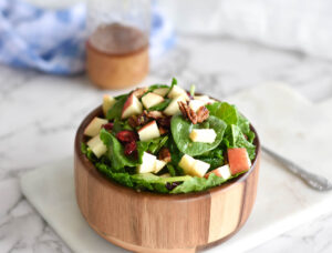 Wooden bowl on white marble serving board. Bowl is filled with green spinach, red apples, cranberries and pecans.