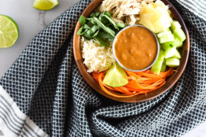 Wooden bowl filled with ginger, basil, rice, cucumber and chicken wrapped in a towel.