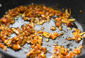 Browning tomato paste in frying pan with onions and garlic