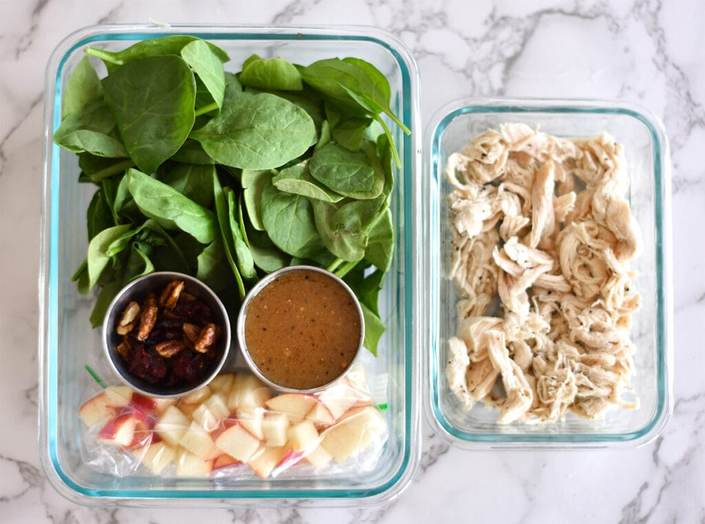 Meal prepped apple salad with apples, pecans, cranberries, spinach and chicken.