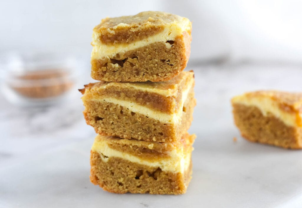 Stack of blonde brownies with cream cheese swirl.