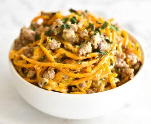 White bowl filled with spiralized butternut squash noodles, creamy parmesan sauce and sausage.