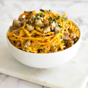 White bowl filled with spiralized butternut squash noodles, creamy parmesan sauce and sausage