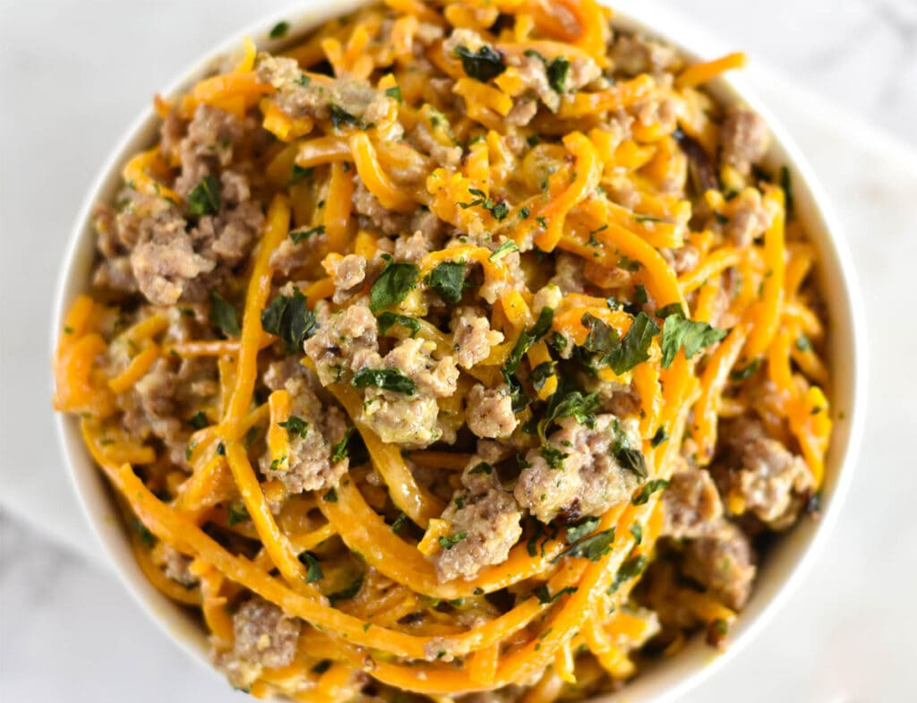 Top down view of butternut squash noodles with sausage and basil.