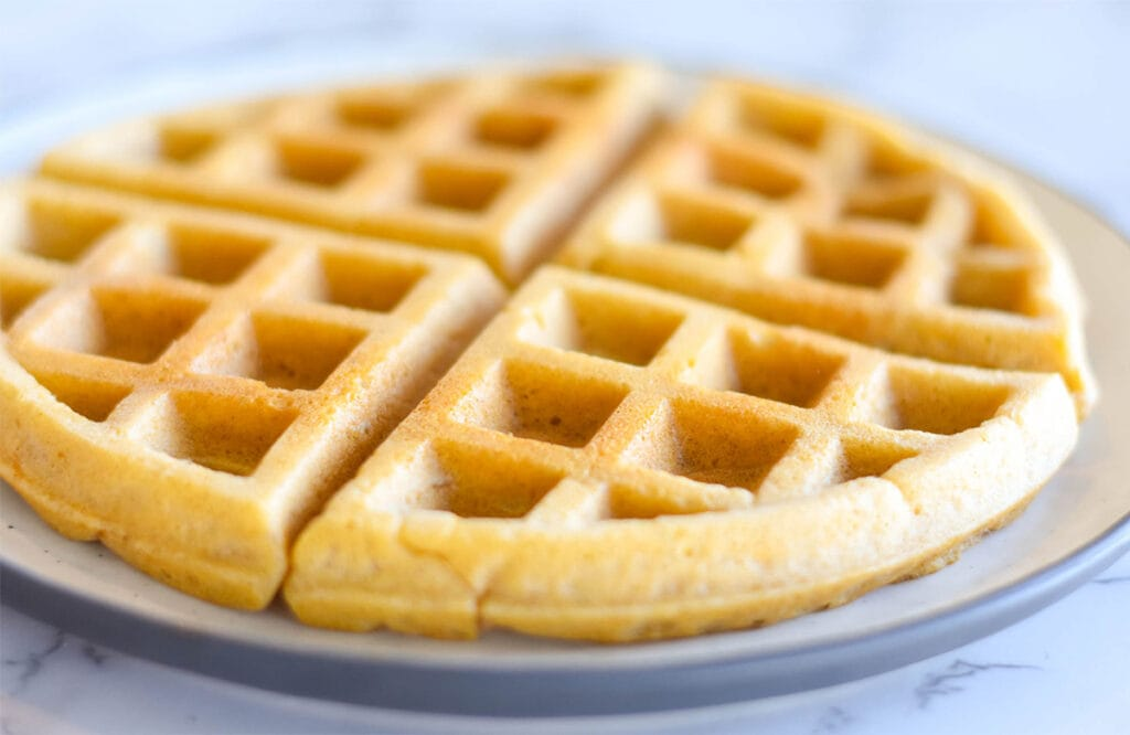 Golden, crispy paleo waffles on a plate.