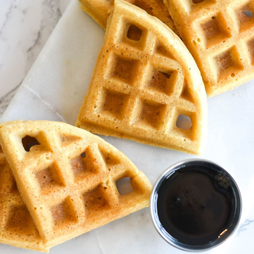 Cut pieces of paleo waffles on cutting board next to syrup for dipping.