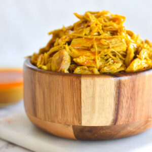 Wooden bowl filled with tandoori chicken curry with white background.