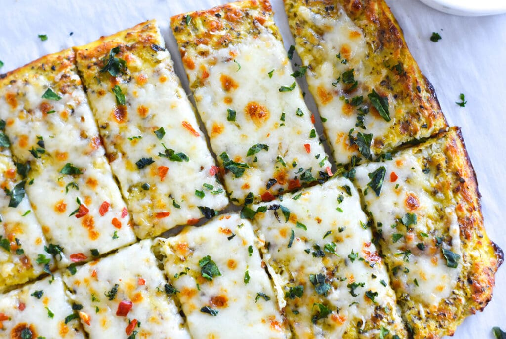 Slices of keto cheesy garlic bread topped with cheese and herbs.
