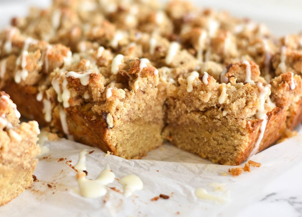Keto cinnamon coffee cake with drizzled icing on parchment paper and one piece removed.