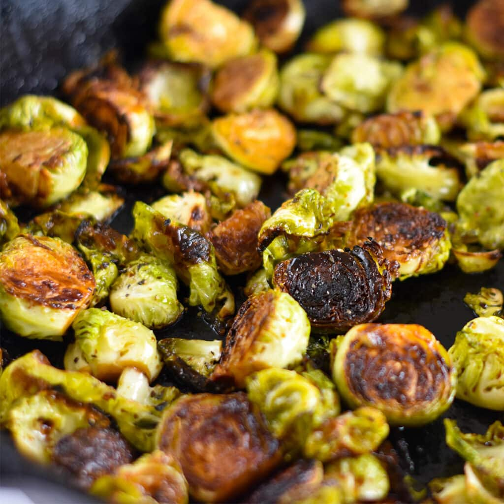 Cast iron skillet filled with caramelized brussel sprouts.