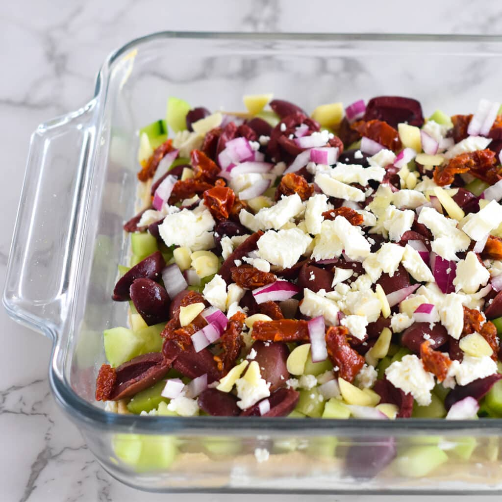 Dish filled with hummus,, feta, olives, ricotta, garlic, onions, cucumber and sundried tomatoes.