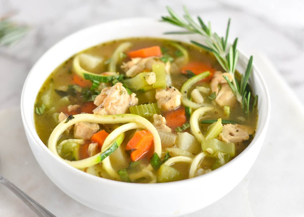 Paleo Chicken Zoodle Soup in a white bowl with carrots, potatoes and chicken breast.