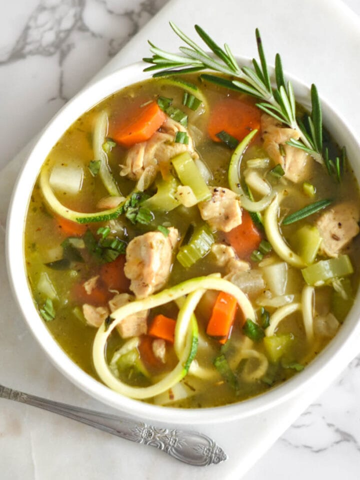 Paleo Chicken Zoodle Soup in a white bowl with carrots, potatoes and chicken breast, garnished with rosemary on a white cutting board.