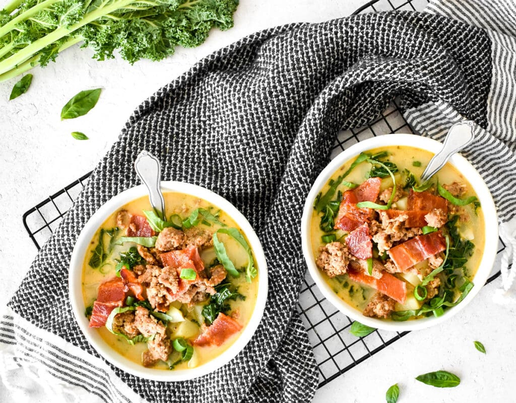 Two white bowls wrapped with a black towel filled with kale, sausage, potatoes, basil, green onion and a creamy yellow broth.