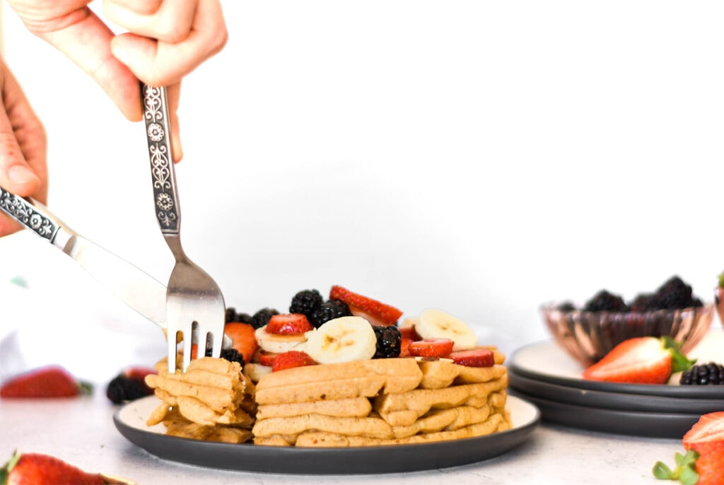 Fork and knife cutting into paleo waffles covered in bananas, blackberries, strawberries and almonds.