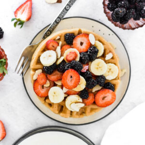 Plate of waffles covered in bananas, blackberries, strawberries and almonds.