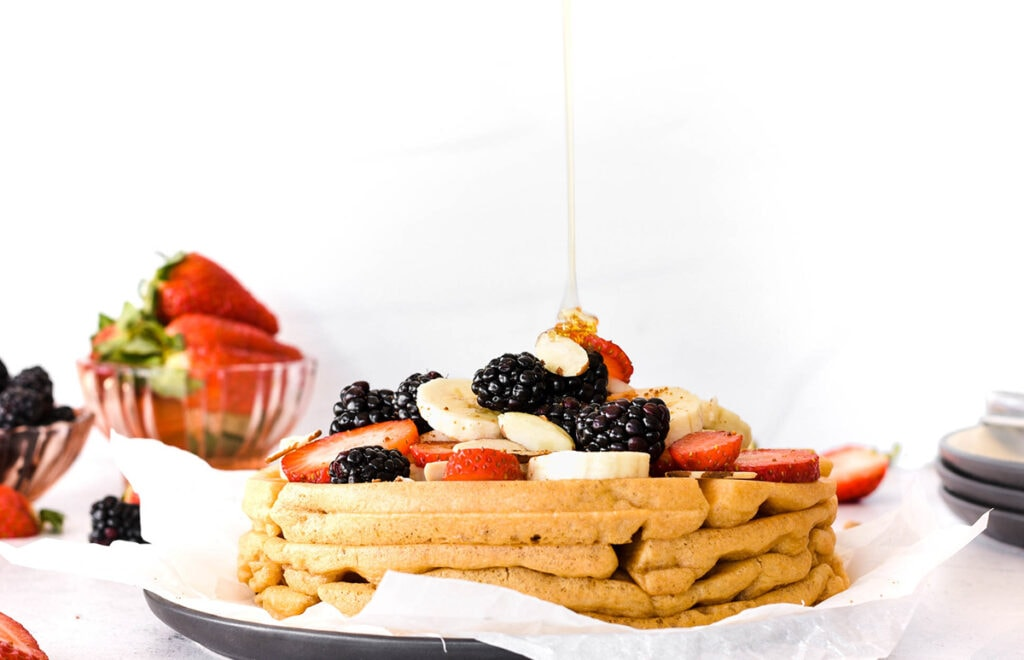 Plate of paleo waffles covered in bananas, blackberries, strawberries and almonds with syrup dripping on top.