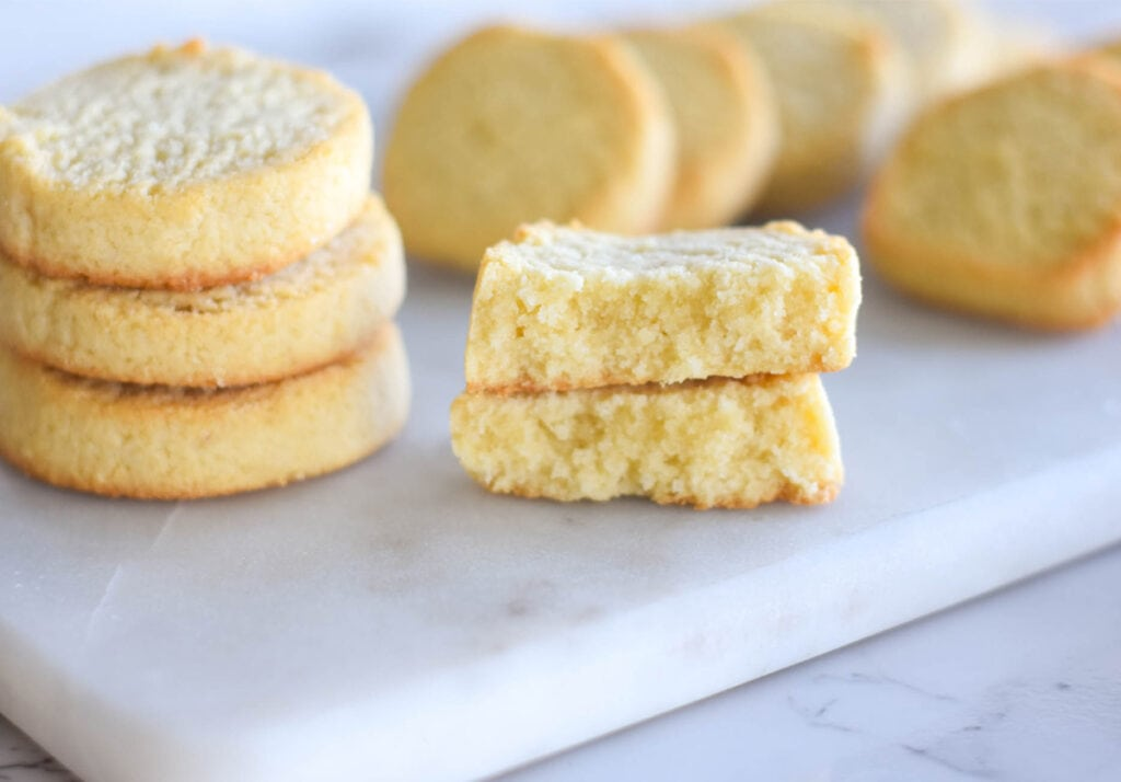 Stack of three golden buttery keto shortbread cookies with one broken in half to show the inside.