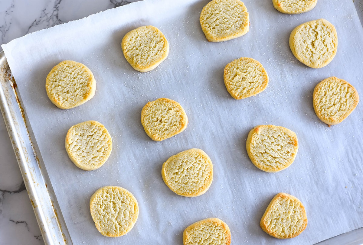DBaking sheet lined with parchment paper with round buttery shortbread cookies.